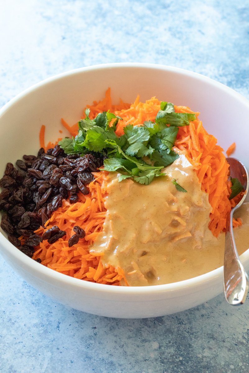 carrots, raisins, tahini dressing, and cilantro in a bowl before mixing