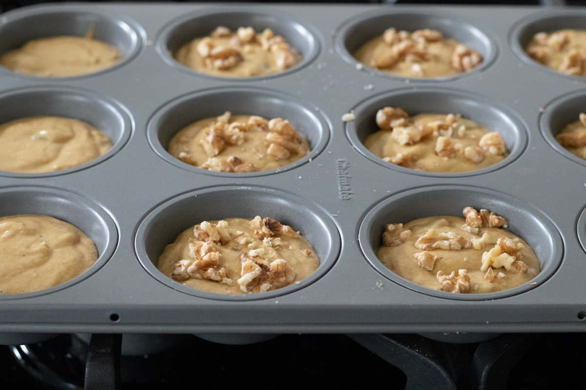 filling muffin pan with batter