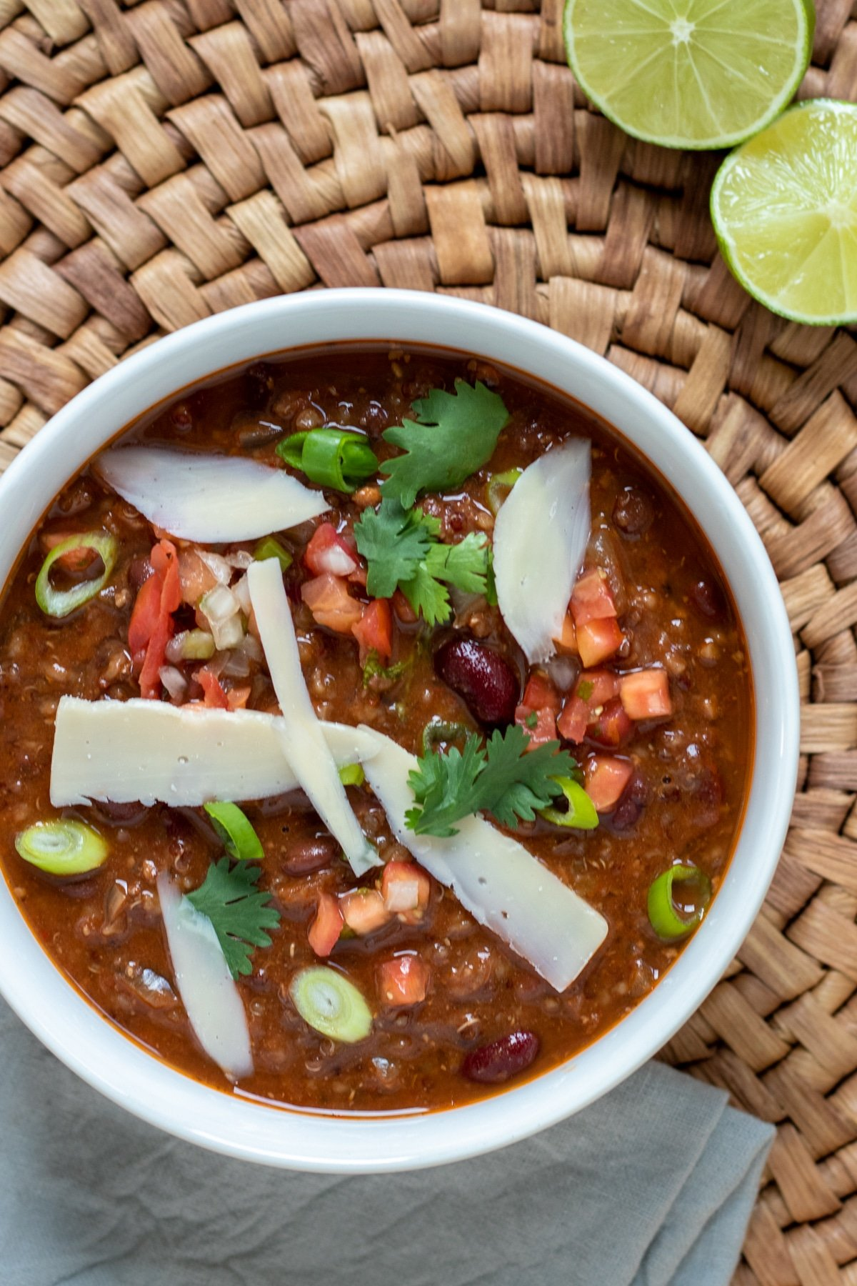 vegan chili in a white bowl with toppings