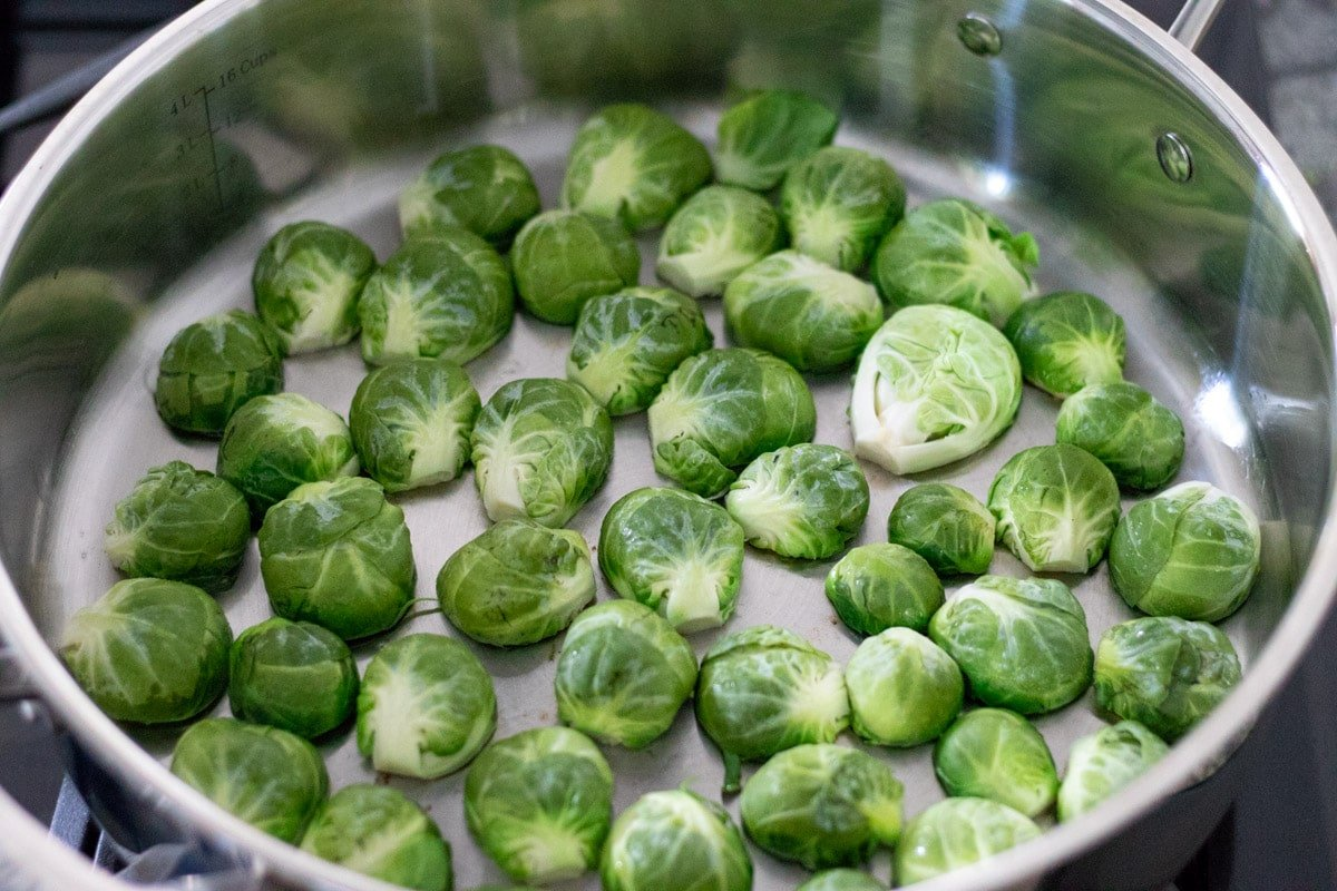 searing brussels sprouts cut-side down in a pan