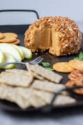 vegan cheese ball on a platter with crackers and apple slices