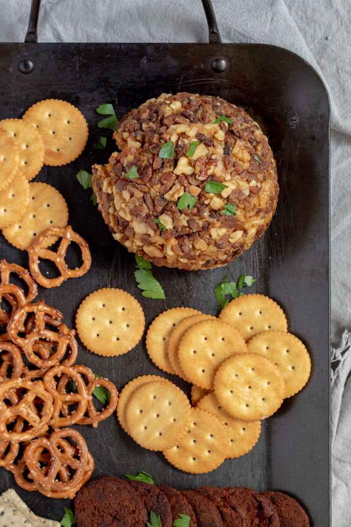 vegan beer cheese ball on a platter with crackers and pretzels