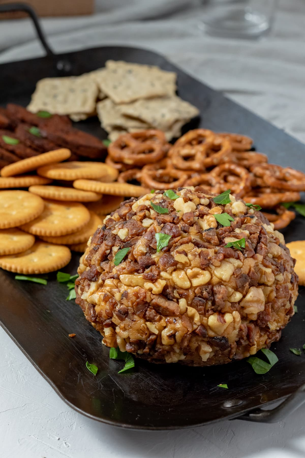 cashew cheese ball coated with vegan tempeh bacon and walnuts sitting on a platter