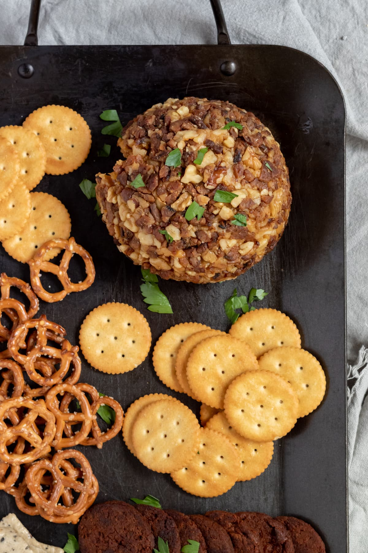 vegan cheese ball on black platter with crackers and pretzels