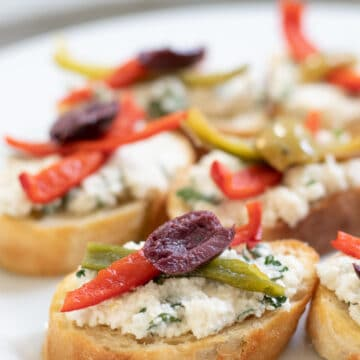 Vegan Crostini with herbed almond ricotta on a white plate