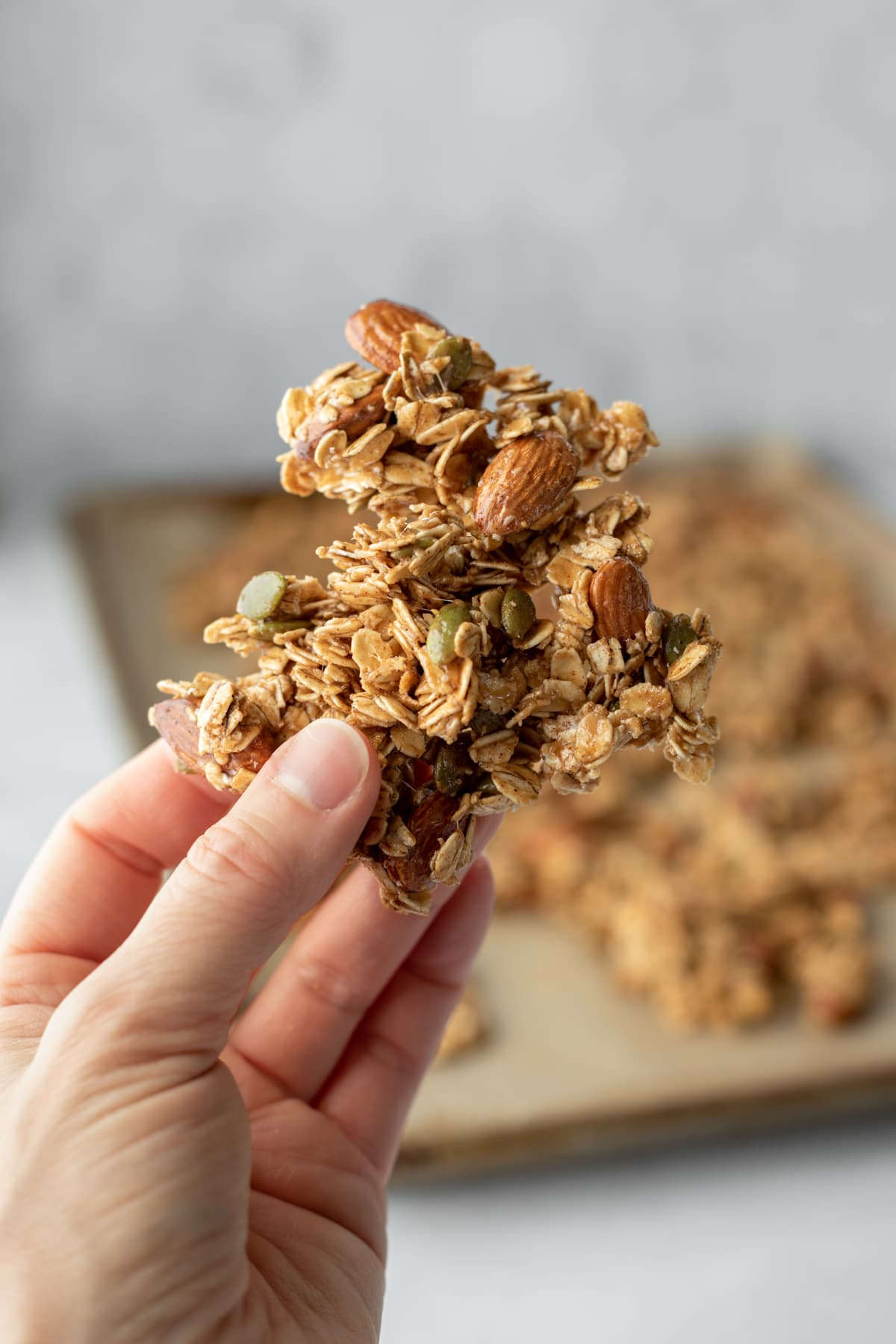 hand holding up a big cluster of granola