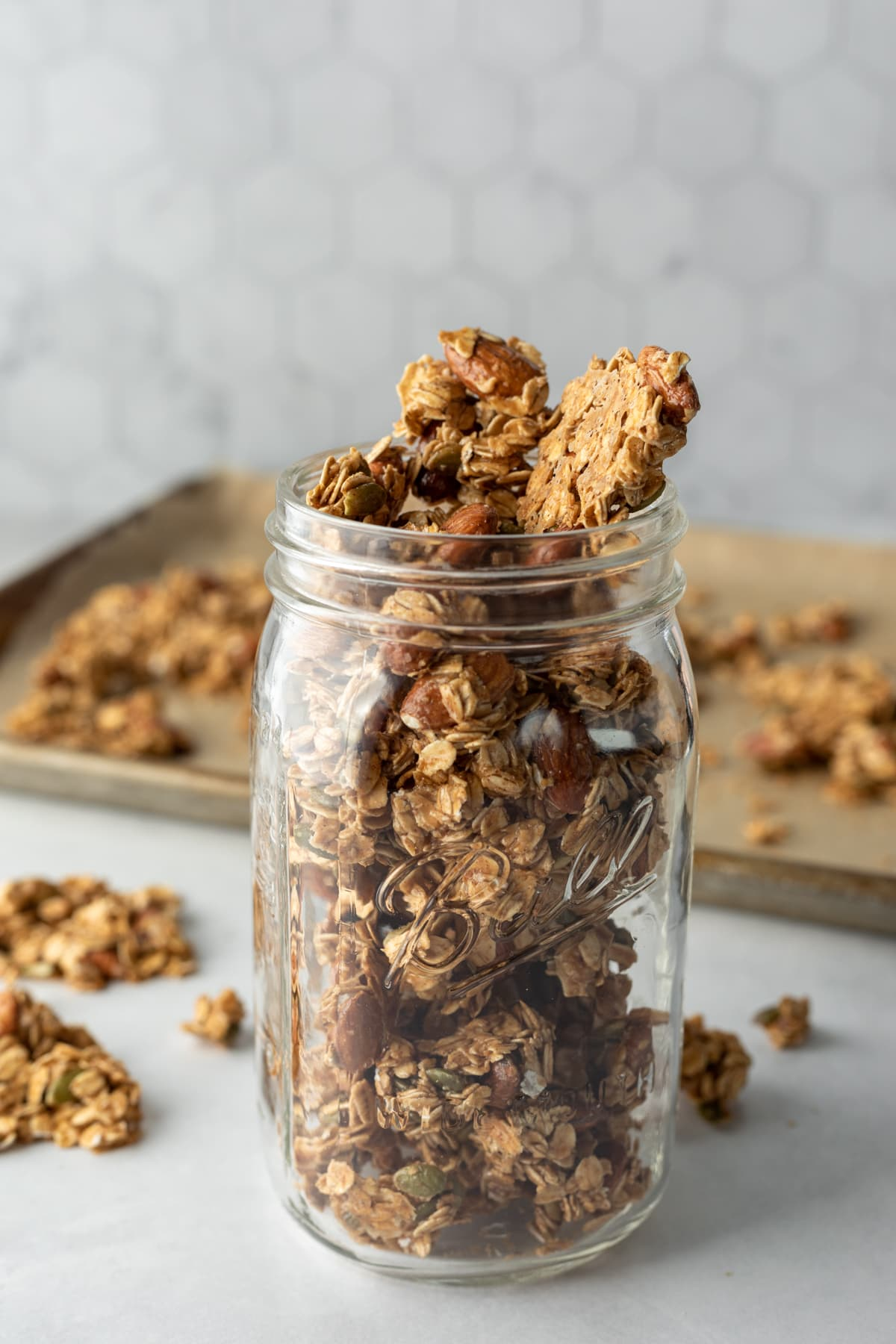 mason jar filled with granola clusters with baking sheet in background