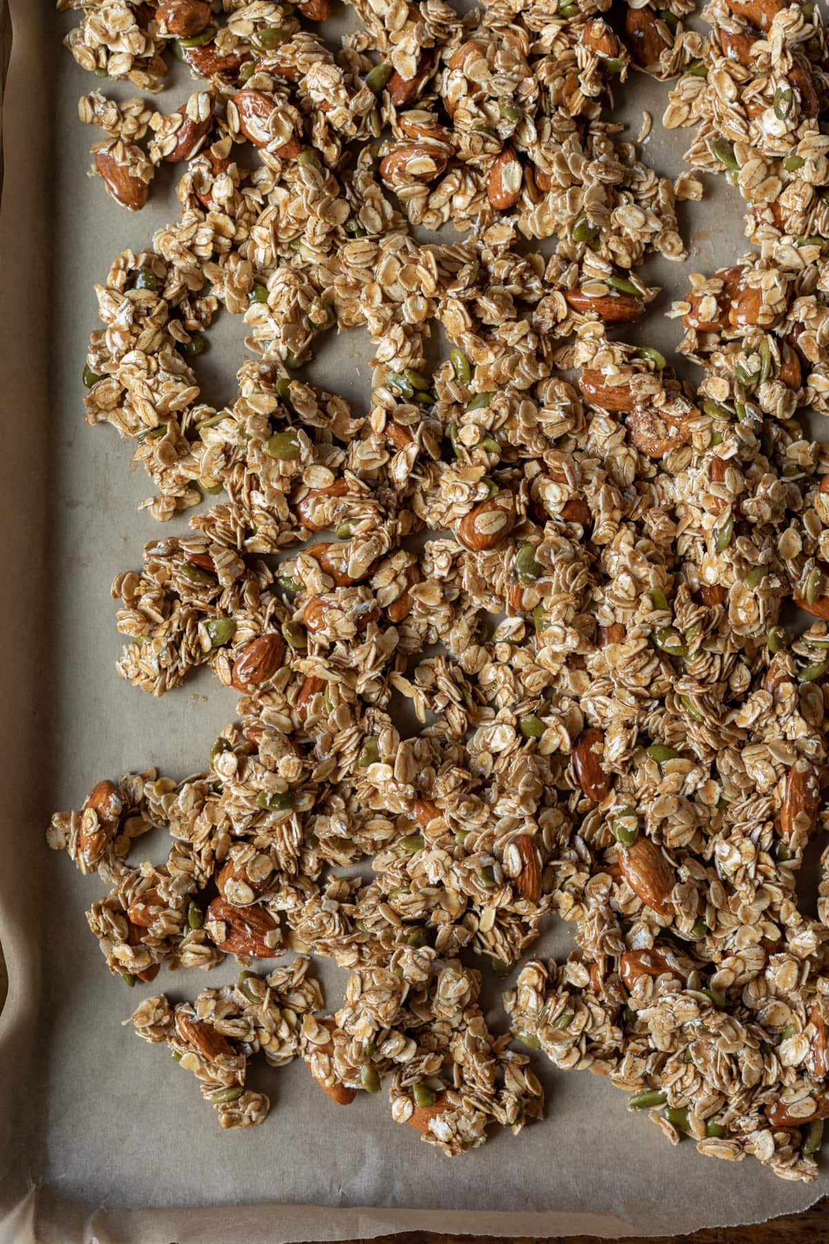 showing how to spread granola out on pan to bake; it's okay if there is overlap
