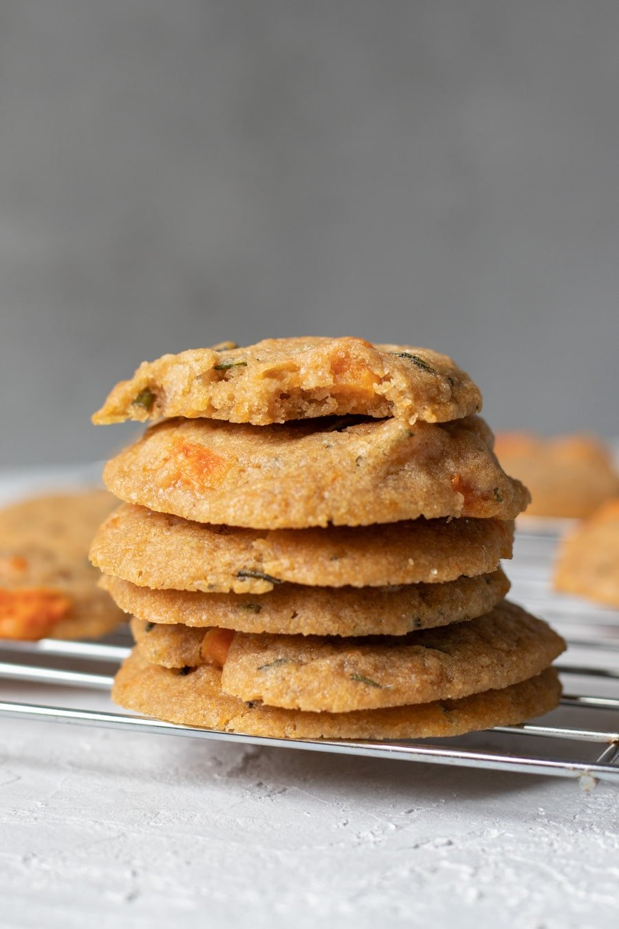 Roasted Honeynut and Rosemary Cookies stacked on a cooling rack