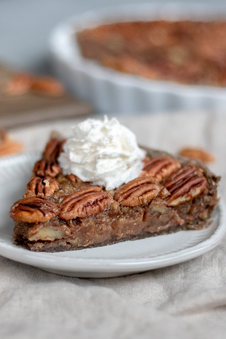 a slice of Vegan Bourbon Pecan Pie with whipped topping