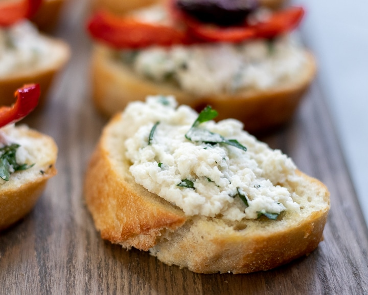 Almond ricotta mixed with fresh herbs spread on toasted baguette