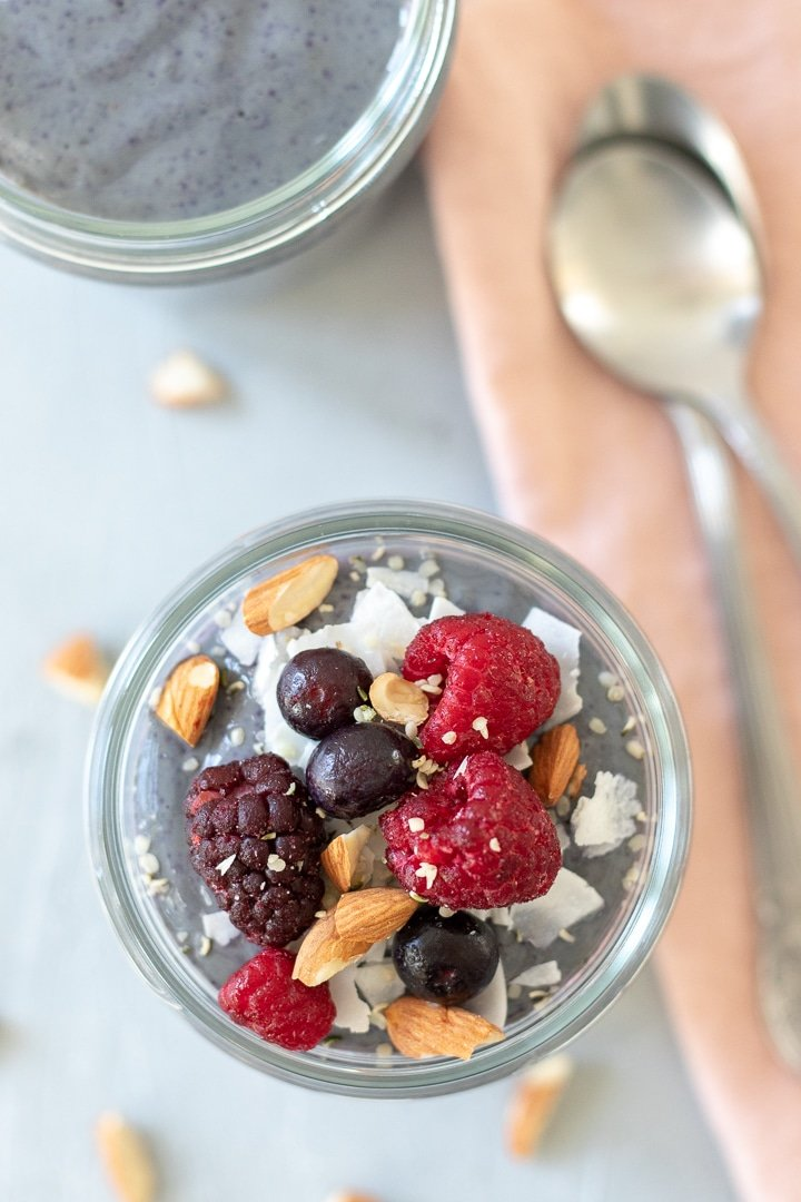 overhead shot of Berries and Greens Breakfast Pudding topped with coconut, berries and almonds