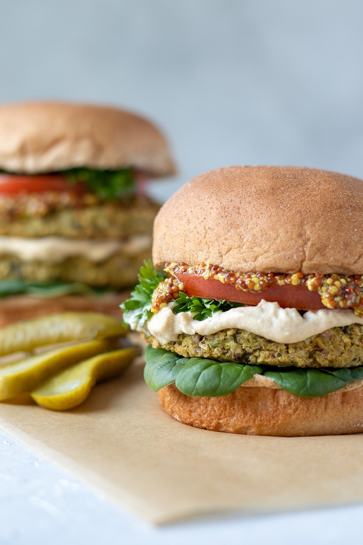 Tabbouleh Bean Burgers on buns with spinach, tomato, hummus and a pickle