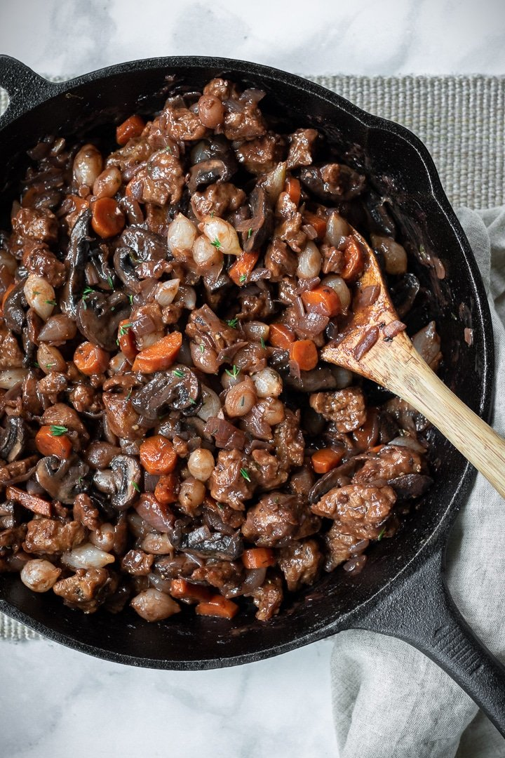 Vegan Seitan Bourguignon in a cast iron skillet with a wooden spoon