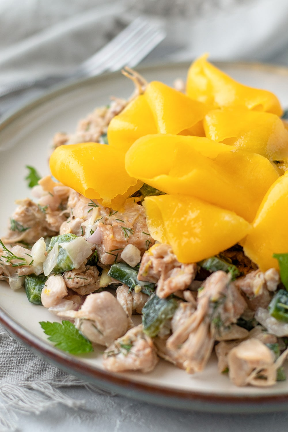 close up of jackfruit salad with fresh herbs and mango ribbons arranged on top