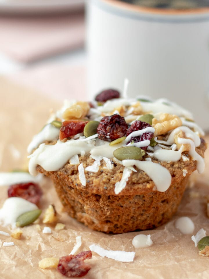 close up of a muffin topped with glaze, seeds, nuts, and dried fruit