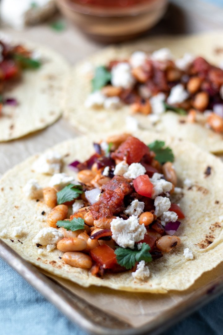 Smoky White Bean Tacos topped with salsa, cilantro and Almond Queso Blanco