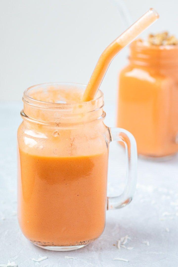 Carrot Cake Smoothie in a glass mug with a glass straw
