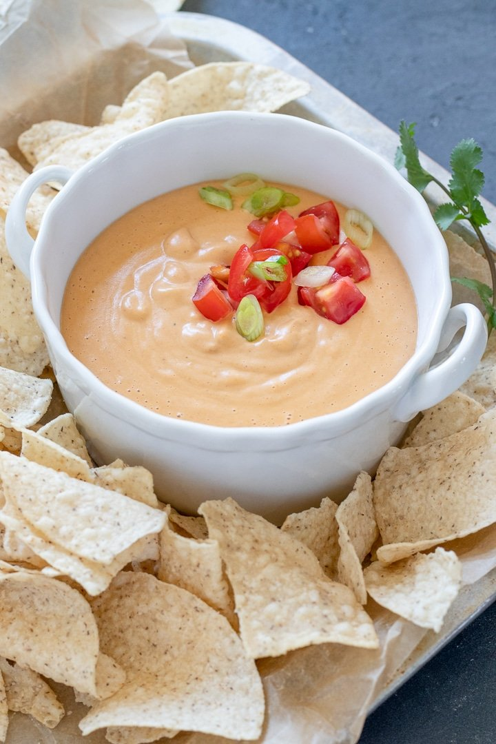 Creamy Vegan Queso in a white bowl topped with tomato and green onion
