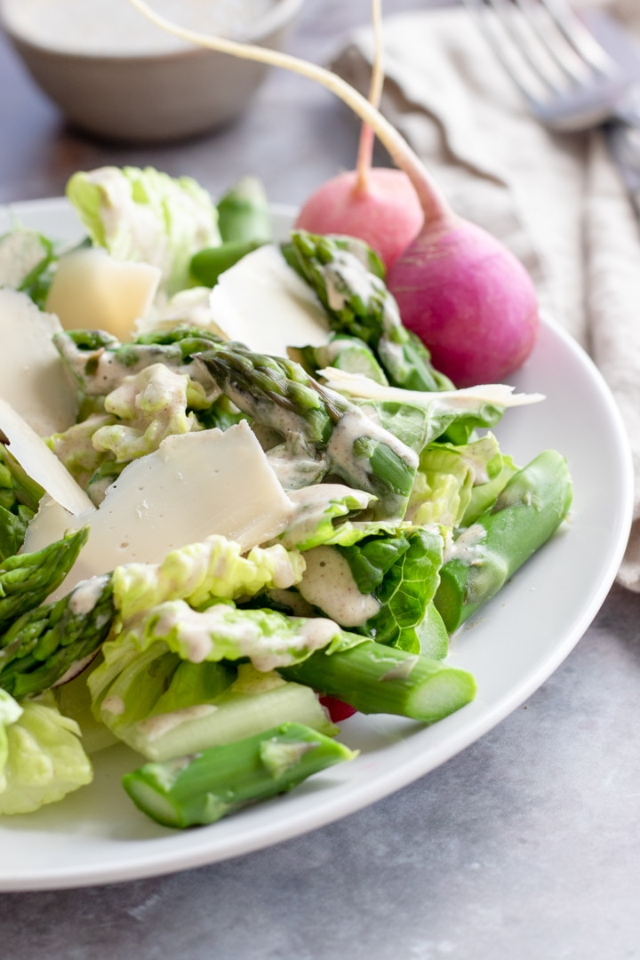 asparagus salad on a white plate with two Easter egg radishes