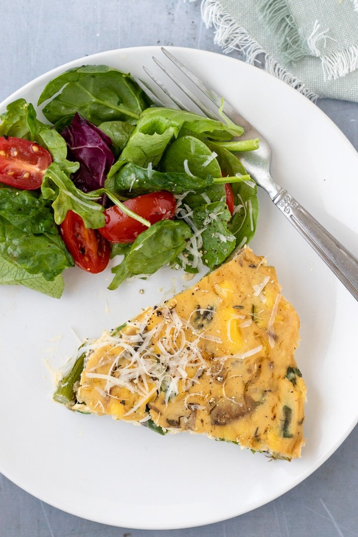 a slice of vegan quiche on a white plate