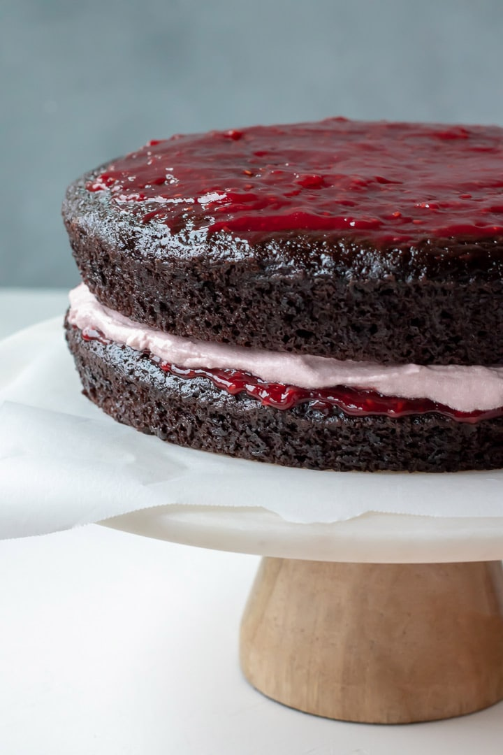 layers of chocolate cake spread with raspberry jam, then raspberry frosting, sitting on a cake stand