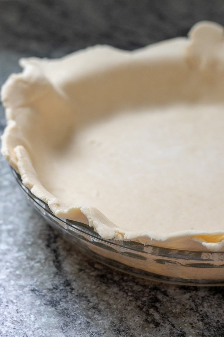 rolled pie dough draped over pie plate