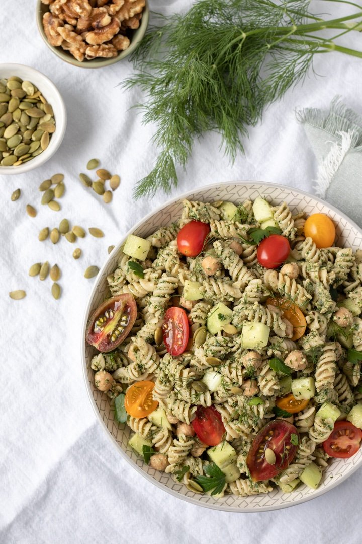 Pasta Salad With Parsley Dill Pesto, tomatoes and cucumbers in a white bowl