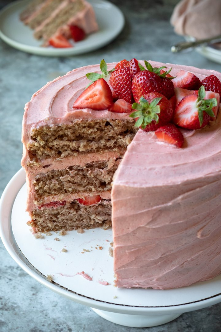 view of the inside of the cake showing 3 layers with fresh strawberries and frosting inbetween