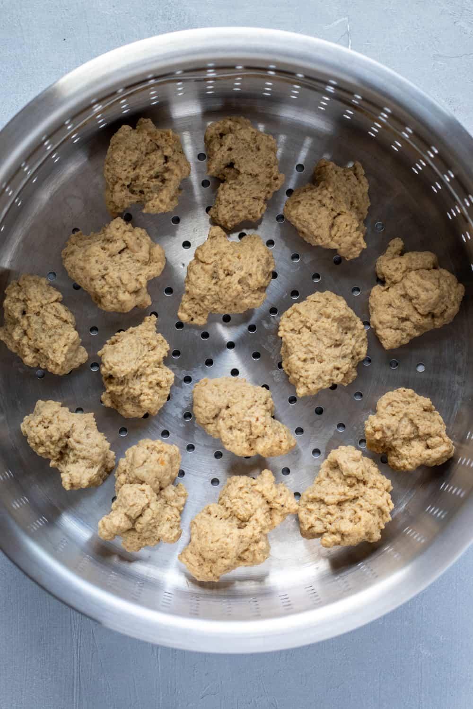 seitan dough torn into smaller nuggets, inside a steamer basket.