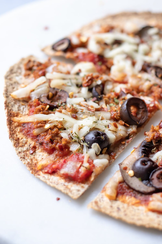 close up of baked vegan tortilla pizza