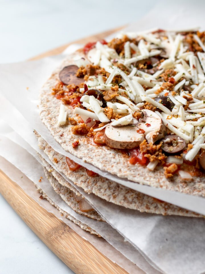 unbaked tortilla pizzas stacked with wax paper between each