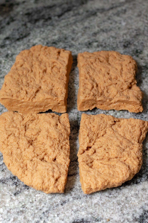 seitan dough cut into four pieces shaped similar to steaks.