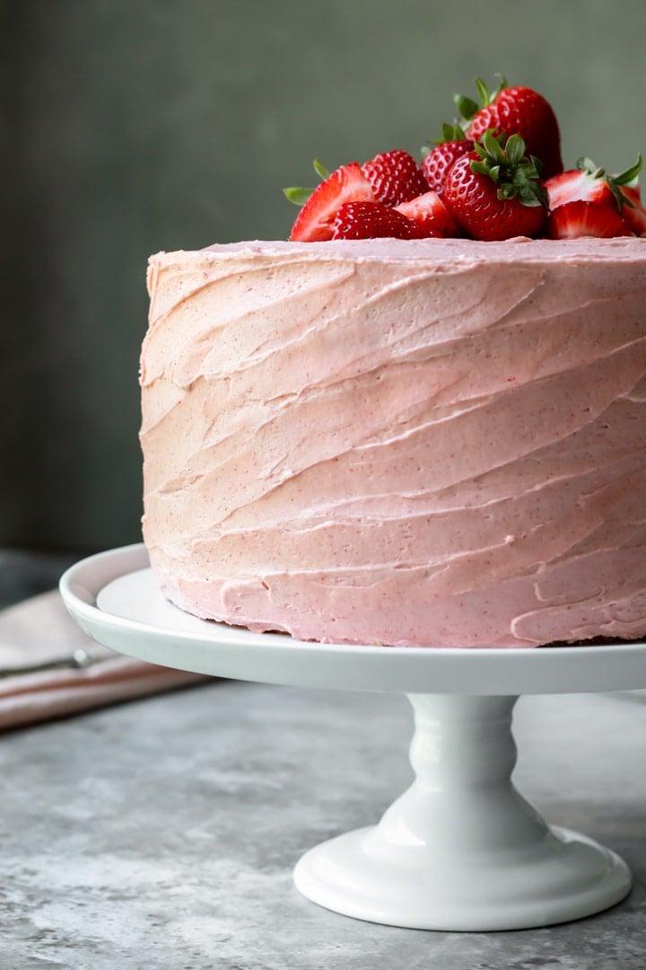 3 layer vegan cake on a white cake stand