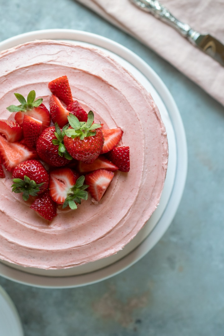 overhead shot of cake decorated with vegan strawberry frosting and fresh strawberries