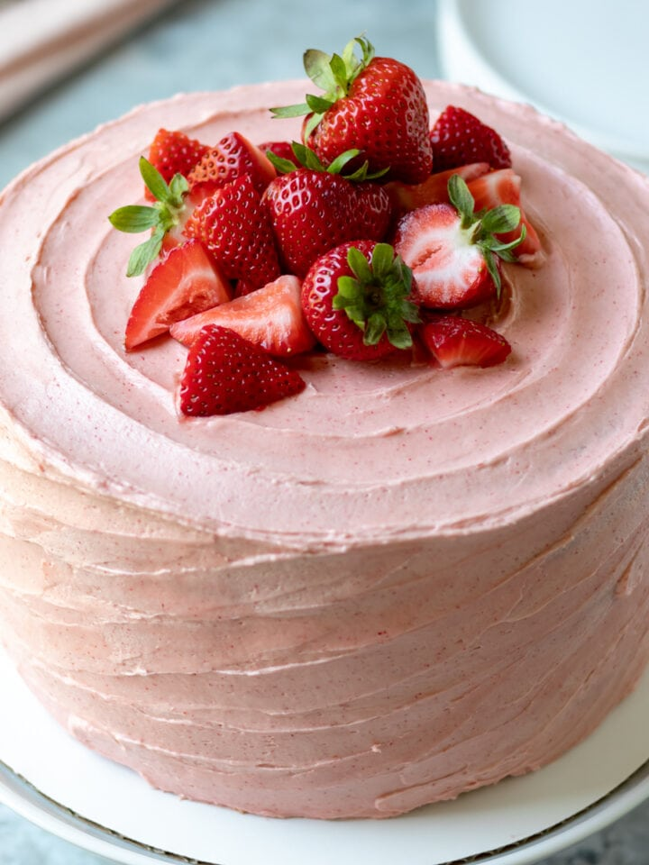 whole 3-layer cake decorated with pink vegan frosting and strawberries on top