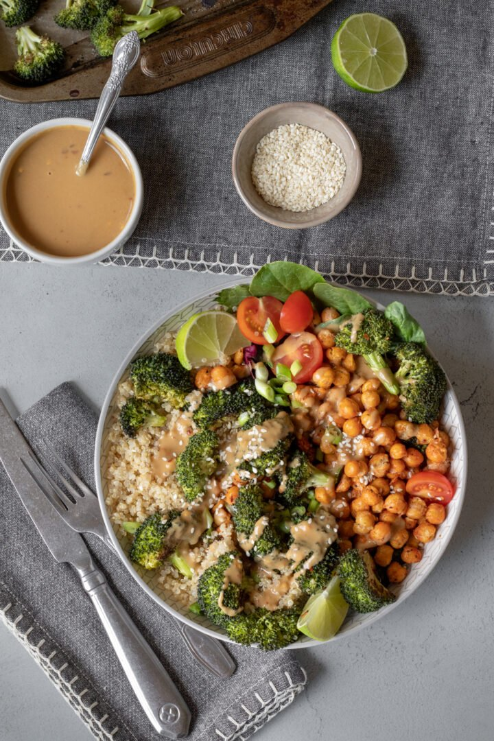 Roasted broccoli, quinoa, roasted chickpeas in a white bowl topped with green onion, sesame seeds and sauce