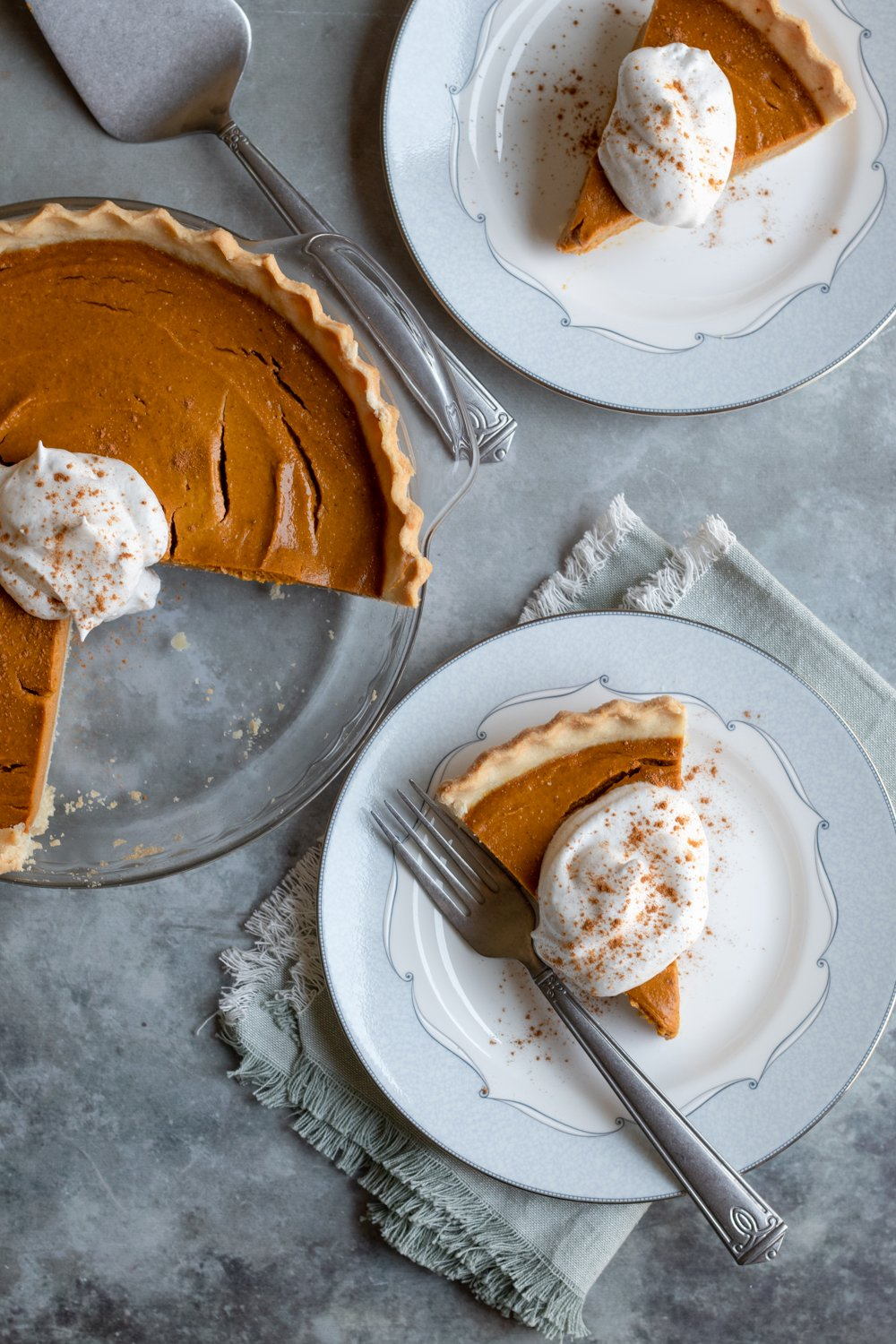 healthy pumpkin pie and 2 slices on plates with vegan whipped cream.