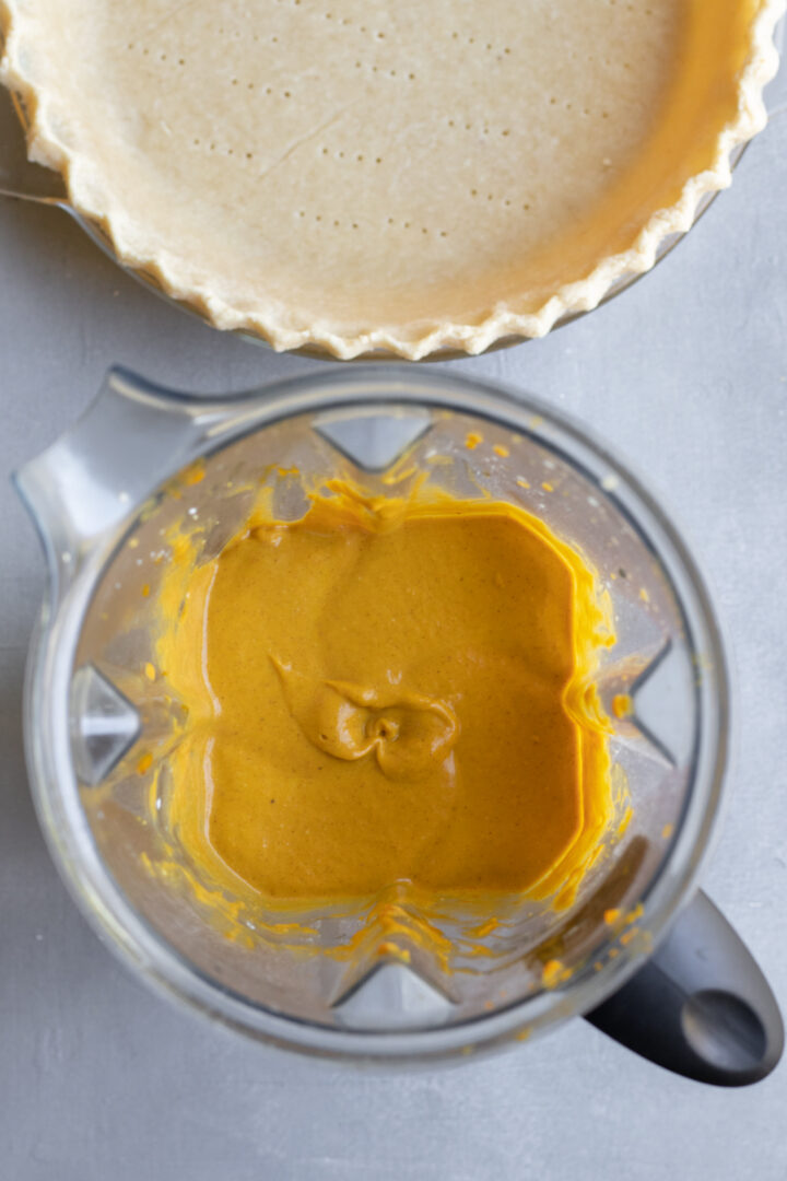 empty pie shell and healthy pumpkin pie mixture in blender