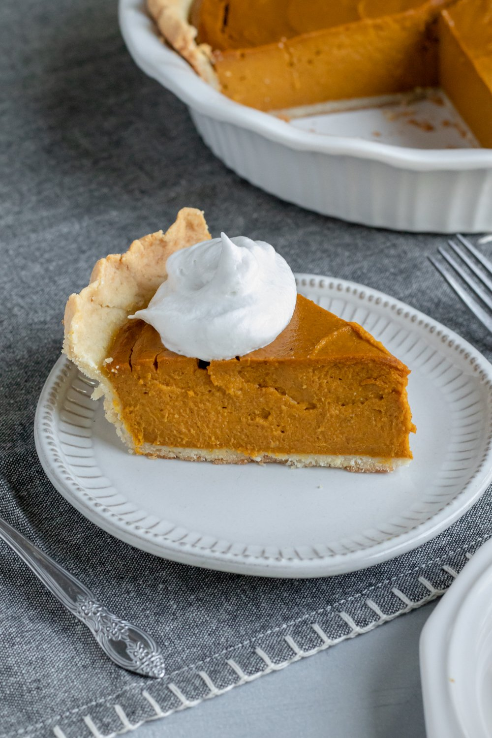 deep dish vegan pumpkin pie topped with So Delicious coconut whipped topping.