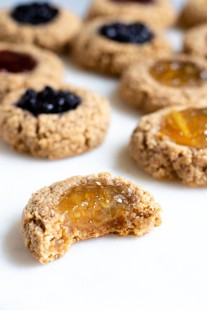 close up of thumbprint cookie with orange jelly