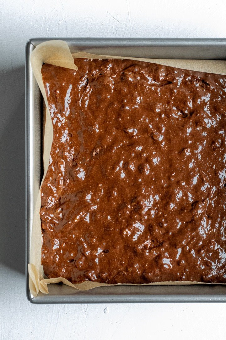 oil-free brownie batter in parchment-lined pan