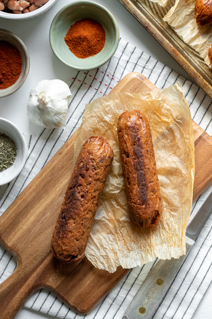 seitan sausages on a cutting board surrounded by spices