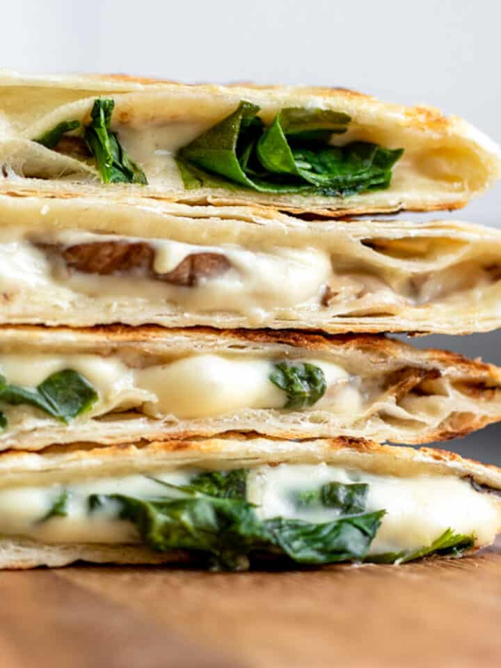 close up side view of sliced quesadillas with spinach. and homemade vegan cheese.