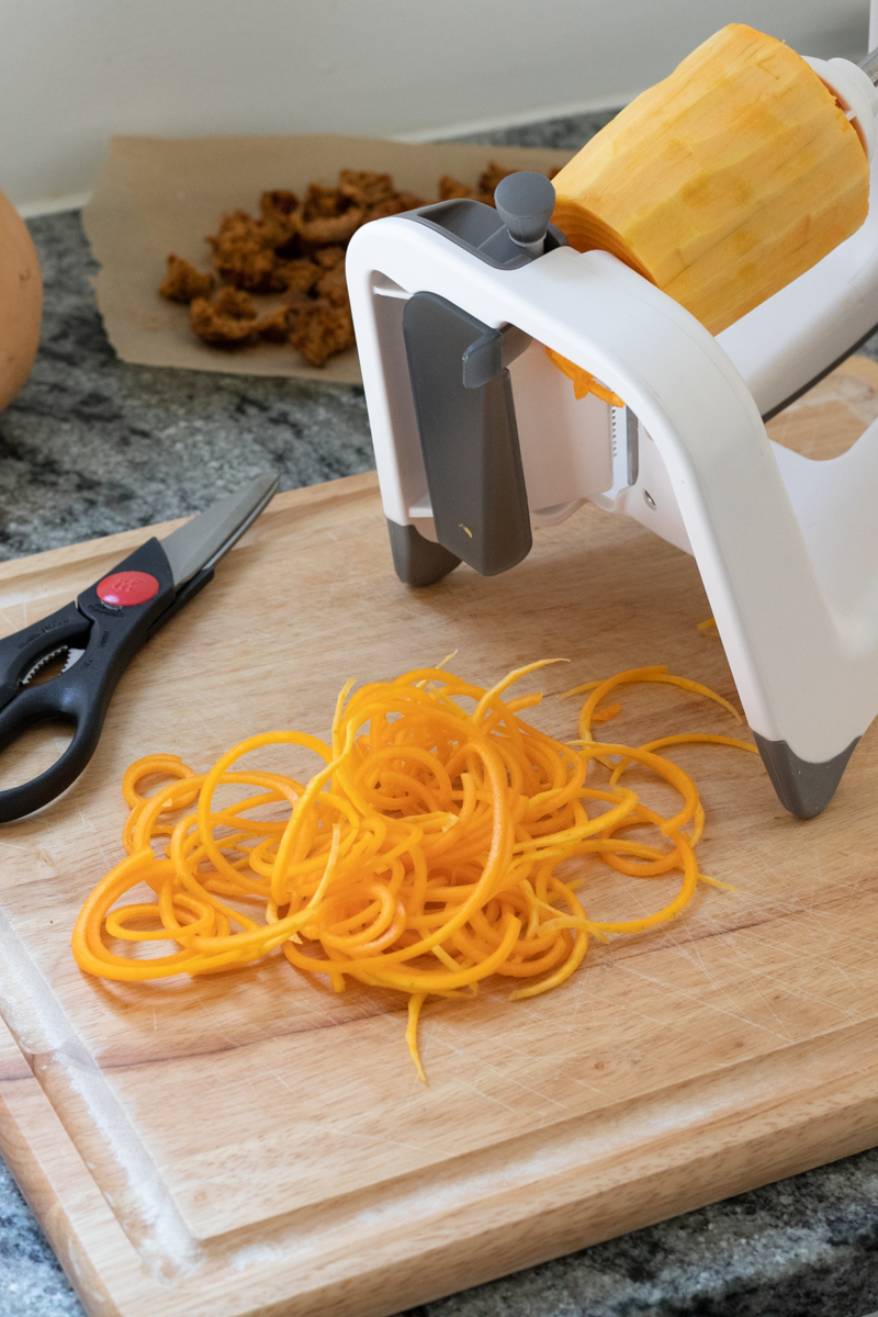 using a spiralizer to create noodles with the neck of a butternut squash
