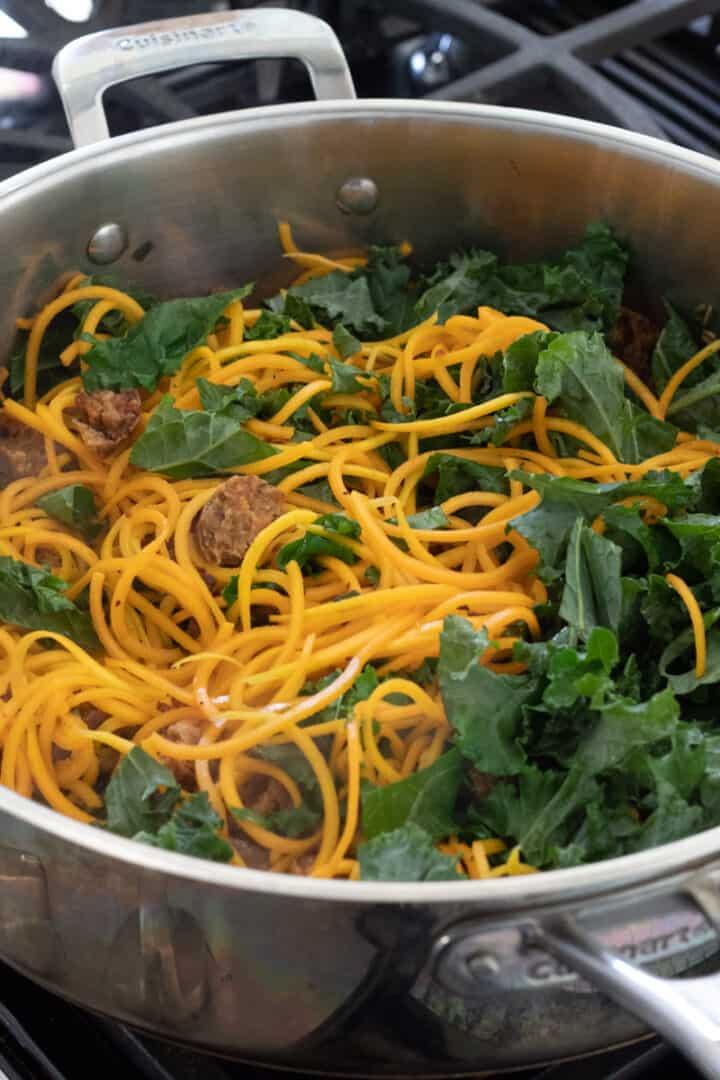 vegan sausage, kale, garlic, sage and butternut noodles in a saute pan