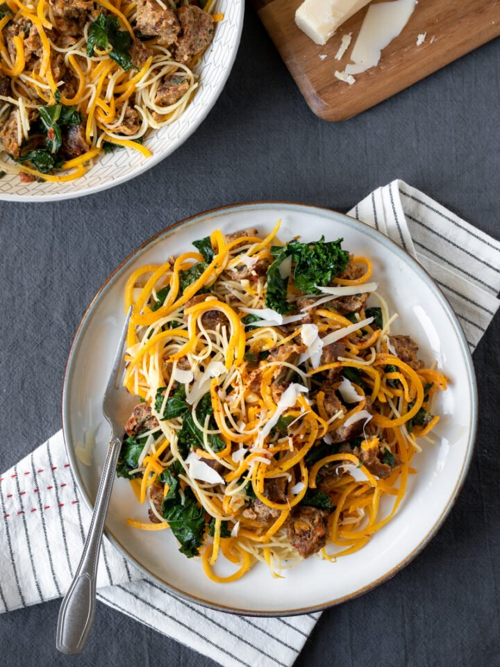overhead shot of butternut squash noodle dish with kale and sausage