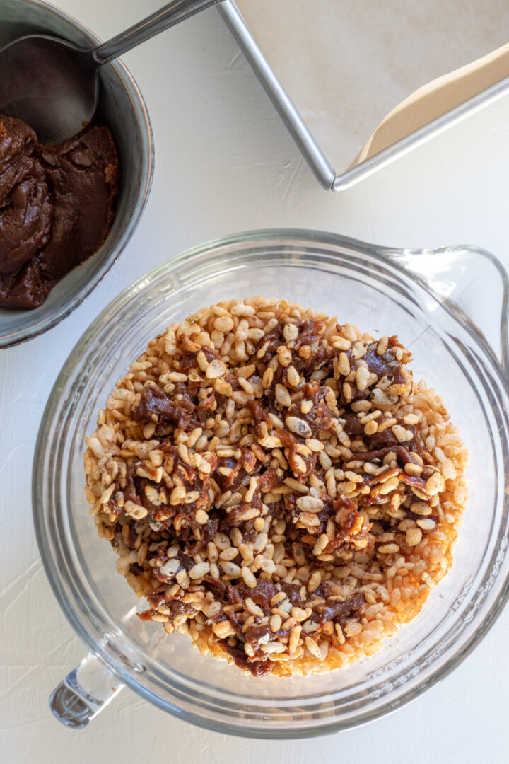 stirring date paste into crispy rice cereal