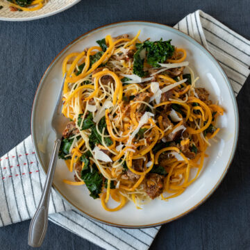 spiralized butternut noodles with kale and sausage on a plate