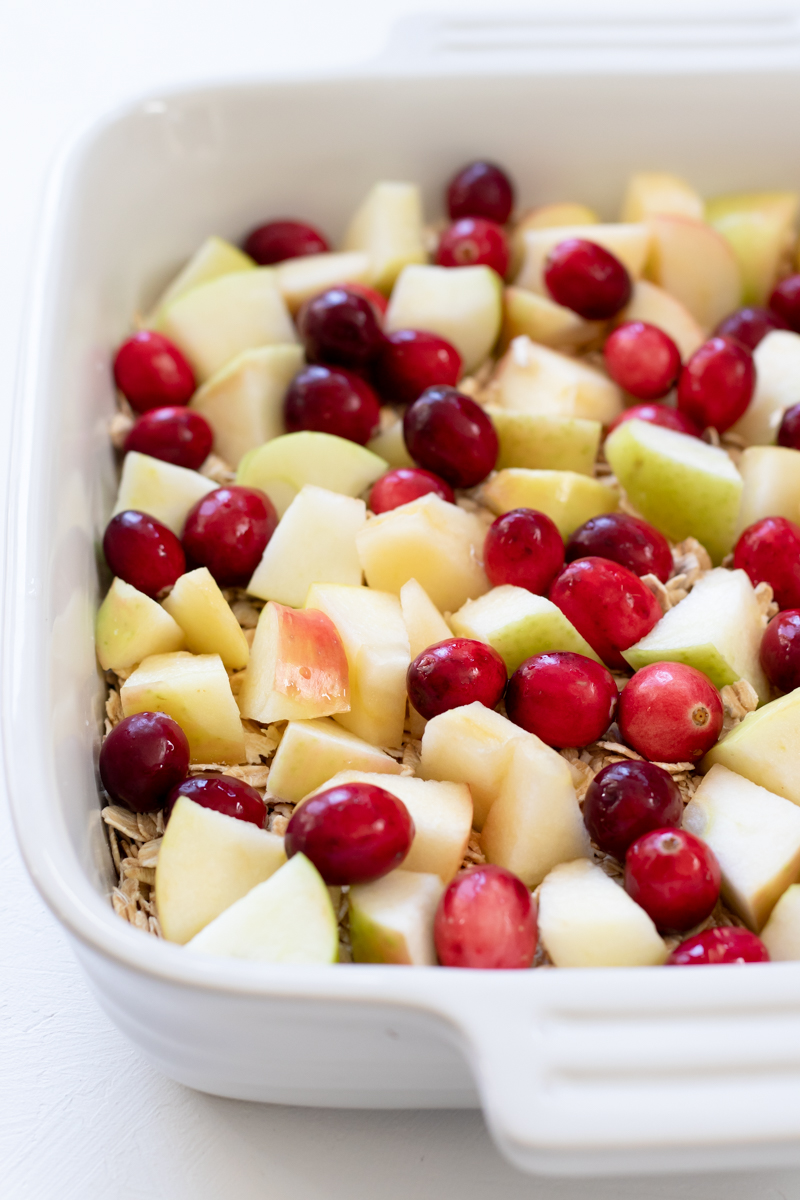 layers of oats, apple, and cranberries in a baking dish